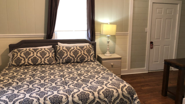 King sized bed at Blackbeard Lodge's east room apartment vacation rental on Ocracoke Island.